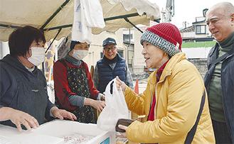 餅を購入する買い物客(右)とスタッフ