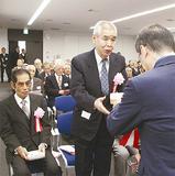 大木節裕区長(右)から記念品を受け取る常木さん(左は加賀美さん)