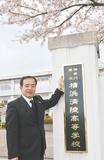 真新しい校名板に手を添える田中校長