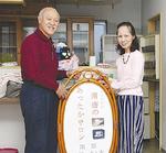 会場の空き家で看板を持つ吉井さん(左)と自治会員