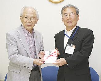 南区社会福祉協議会の大津会長(左)に目録を手渡す桃井事務局長