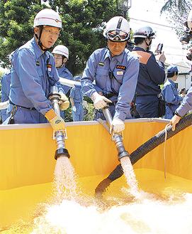 中村川から汲み上げた水を水槽にためる消防団員