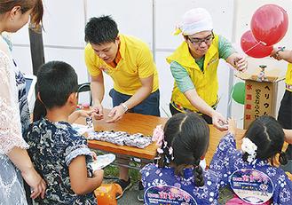 祭りで子どもらに風船を手渡すスタッフ