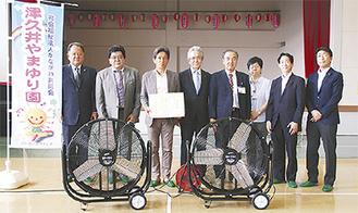 扇風機を前に記念撮影を行う西田会長(左から3人目)、草光理事長(同4人目)ら
