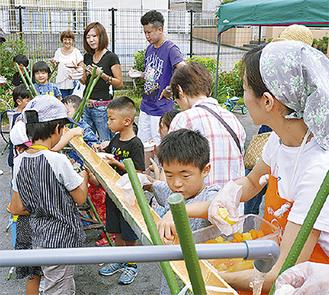 そうめんが流れる竹の筒を囲む子どもら