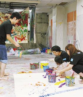空き店舗内で布に絵を描く子ども