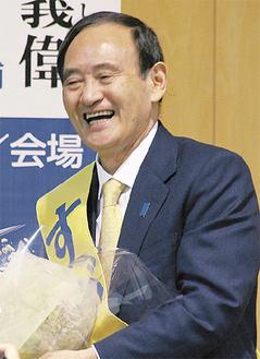 集会で花束を受け取り、笑顔を見せる菅氏(19日、蒔田中)
