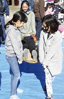 棒と毛布の簡易担架で人を運ぶ子ども
