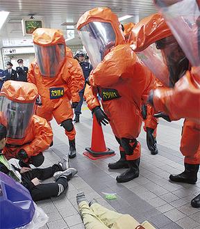 負傷者役を救助する化学防護服を着た隊員