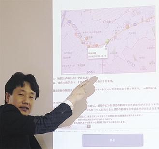 スマートフォンの画面で地図上に表示される受信ポイントについて説明するALSOKの担当者