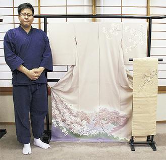 桜で染めた帯と桜の風景を描いた着物の横に立つ吉原慎太郎さん