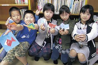 折り紙で作ったかぶとや金魚を手にする子どもたち