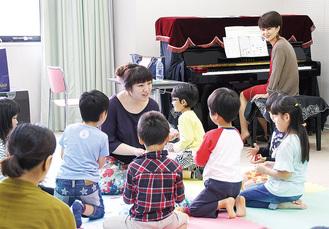 堀口さん(中央)と歌う子ども