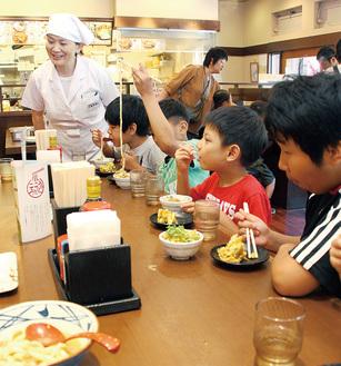 試食する児童と協力した店員の北見さん(奥)