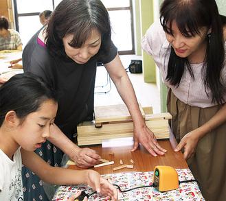 粟津さん(右)と平沼さん(中央)から指導を受ける小学生