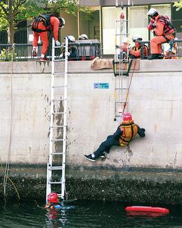 救助器具を付けられて引き上げられる水難者役