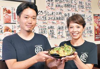 XO醤炒飯を手にする能登谷さん(左)