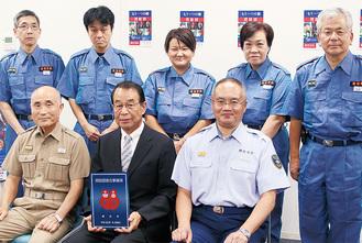 協力事業所の表示証を手にする佐藤院長(前列中央)と入団した職員(後列)。前列左は涌井団長、右は小出署長