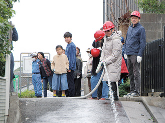 放水を行う参加者。写真右側が上町第一町内会、左側が北ノ前町内会の範囲