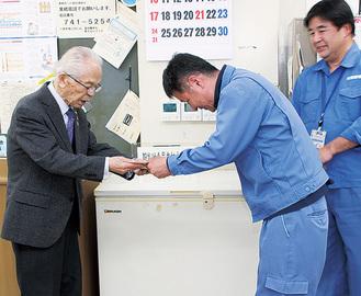 大津会長(左)に募金を渡す職員