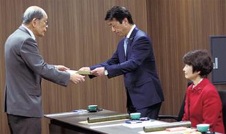 山田委員長(左)から当選証書を受け取る新堀史明氏(右は岸部都氏)