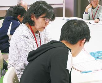 生徒に問題集の説明をするボランティア