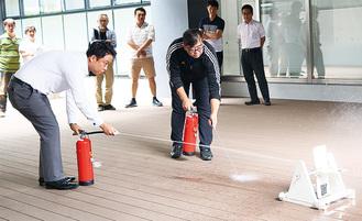 水消火器で消火の練習をする参加者