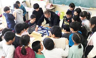 内藤さん(中央)の話を聞く児童(同校提供)