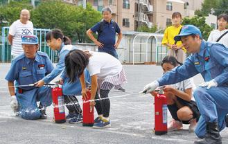 水消火器を扱う子ども