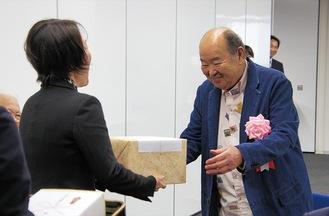 松山区長(左)から記念品を受け取る岩田さん