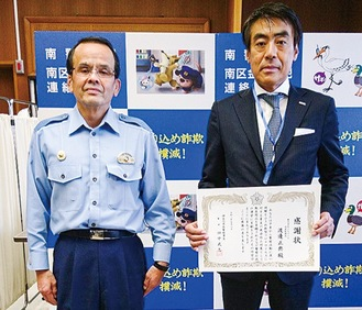 南警察署の田中武志署長(左)から感謝状を受け取ったメモワールの渡邊社長