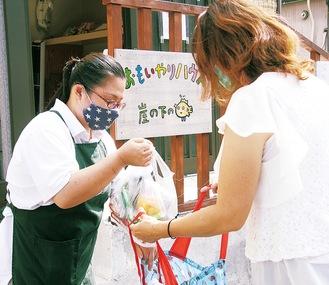 「おもいやりハウス」で津ノ井さん(左)から食料品を受け取る女性