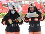 英語、中国語でアナウンスした消防団の高橋さん(左)と林さん