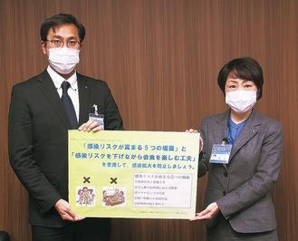 感染防止の注意点が書かれたボードを手に区民に対策を呼び掛ける野崎センター長(左)と松山区長