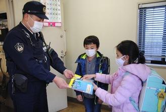 大池交番の署員(左)に絵本を渡す児童