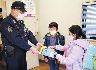 署員(左)に絵本を渡した3年生