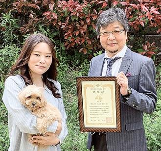 認証状を持つ大山社長(右)と看板犬のティアラを抱く吉田さん