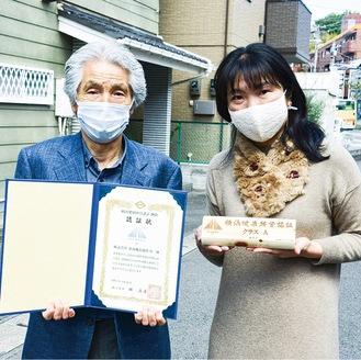 認証状を持つ内田社長(左)と事務職として活躍する社員