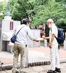 大通り公園にある祈念碑を訪れた人に資料を渡す遺族会の元会員
