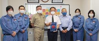 表示証を手にする倉澤社長(中央)と有賀団長(中央左)、今山署長(同右)と団員