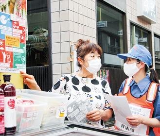 店員(左)に説明する韓国籍団員の金さん