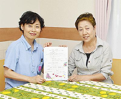 会場で案内書を持つ佐藤さん(右)と「愛あい」の大村さん