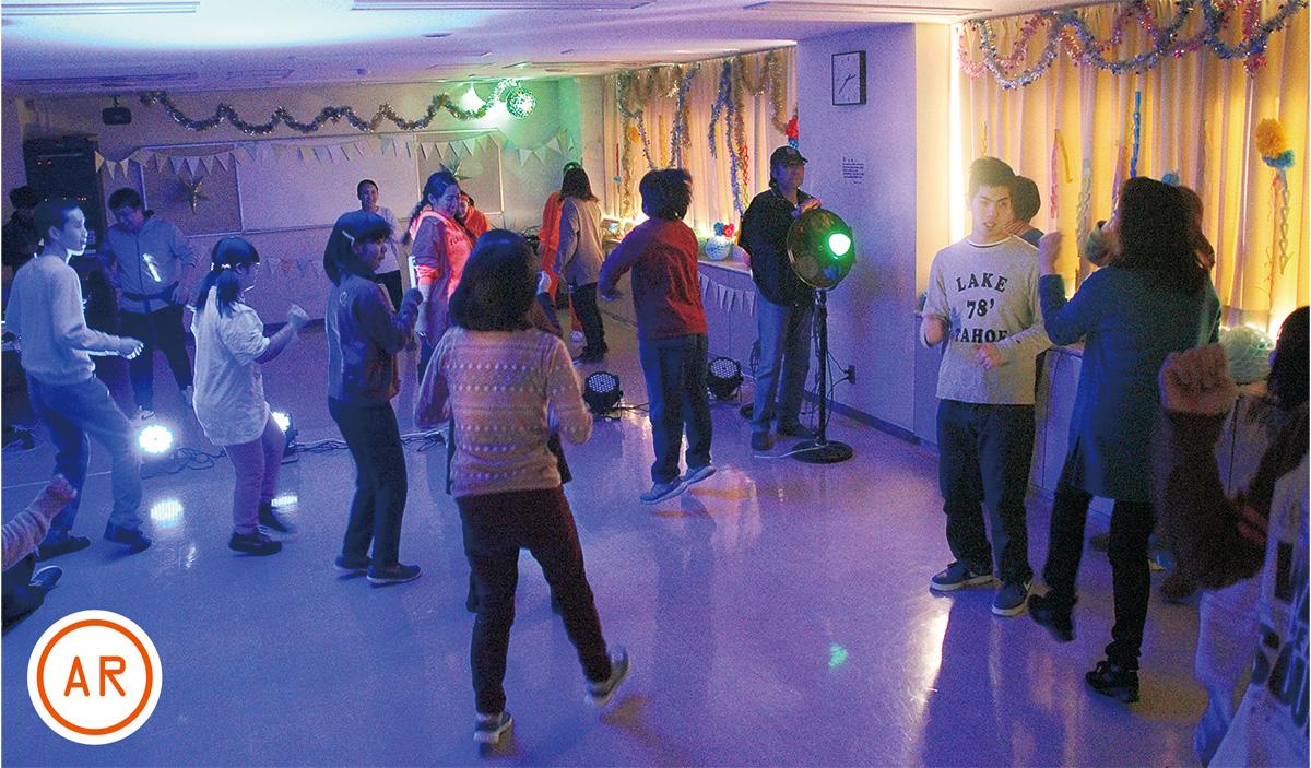 ライトに照らされる中で踊る参加者