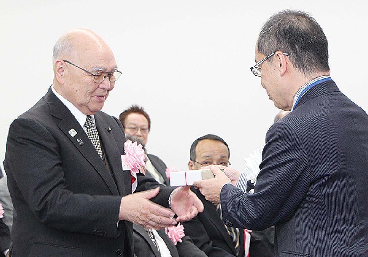 大木区長(右)から記念品を受け取る千葉さん