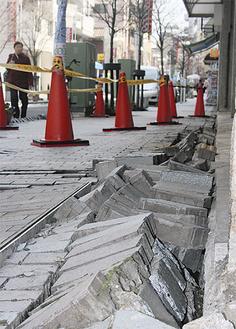 天王町商店街の一角では歩道が大きく破損し、揺れの大きさを物語っていた(12日撮影)
