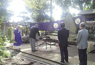 刷毛を供養する塚(中央)に祈りを捧げる参加者たち