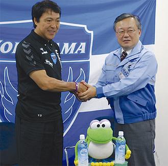 握手を交わす奥寺会長(左)と土井局長(右)