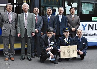 バスの前に集まった関係者と大学職員ら