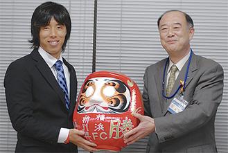 鈴木区長(右)からだるまを受け取った中里選手(左)