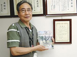 冊子を手にする鈴木会長